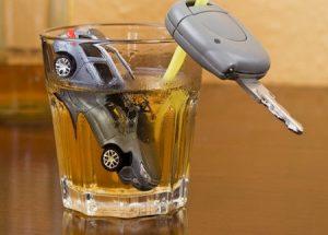 photo illustrant l'alcool au volant avec une voiture miniature dans un verre et une clé accrochée à la paille